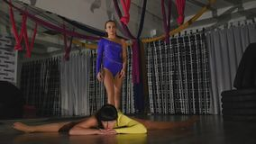 Woman acrobat sits on a string, the other stands on her arms from above stock video footage