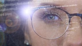 A woman activates a holographic projector in the rim of glasses. Technology software network code. The eyes of a girl software developer code Global data stock video