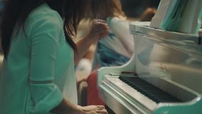Woman actively plays white piano, sitting near restless little girl look inside stock footage