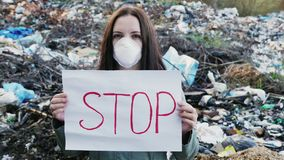 Woman activist with Stop poster on waste dump. Woman activist in respirator mask with Stop poster on the background of a mountain of garbage. Static outdoors