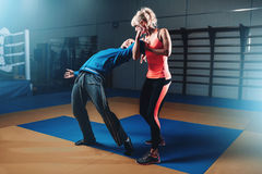 Woman in actoin on self-defense training. With personal instructor, fighting workout in gym, martial art Stock Image