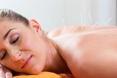 Woman at acupuncture needles in back Royalty Free Stock Image