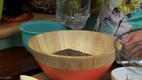 Woman add cumin and water in bowl with bread dough stock footage