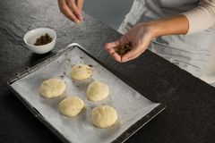Woman adding dry fruits over unbaked cookie dough. In a baking tray Stock Photography