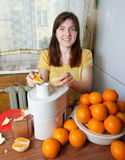 Woman adding orange to juicer Royalty Free Stock Image