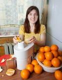 Woman adding orange to juicer Royalty Free Stock Image