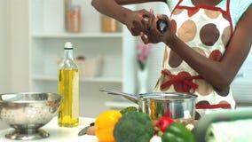 Woman adding pepper to saucepan stock footage