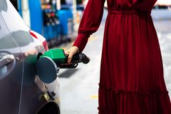 Woman adding petrol on gas station. Woman refiling petrol on gas station close up royalty free stock images