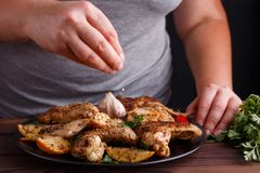 Woman adding salt to grilled chicken wings. Kitchen background, royalty free stock photos