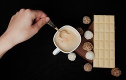 Woman adding sugar in coffee in cafe. Cofe, Stack of Black and White Chocolate isolated on black background, place for text.  Royalty Free Stock Photo