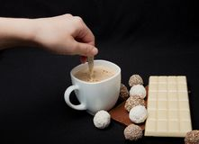 Woman adding sugar in coffee in cafe. Cofe, Stack of Black and White Chocolate isolated on black background, place for text.  Royalty Free Stock Photos