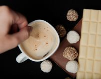 Woman adding sugar in coffee in cafe. Cofe, Stack of Black and White Chocolate isolated on black background, place for text.  Royalty Free Stock Images