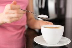 Woman adding sugar to the coffee Stock Images