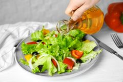 Woman adding tasty apple vinegar into salad. With vegetables on plate stock photos