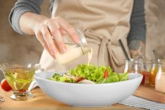 Woman adding tasty sauce to salad in dish. On table royalty free stock photography