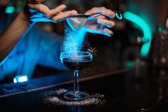 Woman adding to a cocktail decorated with badian a sugar powder through the strainer in the blue light. Woman adding to a cocktail decorated with a badian a stock photos