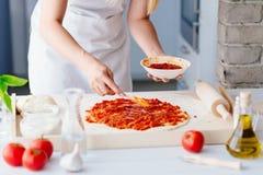 Woman adding tomato sauce on pizza Royalty Free Stock Image
