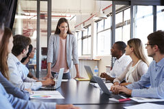 Woman addressing team leans on desk at business meeting Royalty Free Stock Images