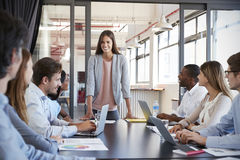 Woman addressing team leans on desk at business meeting Royalty Free Stock Image