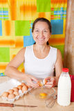 Woman adds eggs into dish Royalty Free Stock Photos