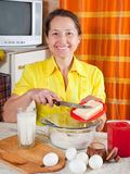 Woman adds margarine into dough. Smiling woman adds margarine into dough in kitchen Royalty Free Stock Images