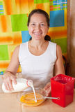 Woman adds milk into dish Stock Photo