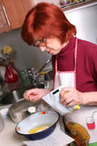 Woman adds milk to the bowl Stock Image