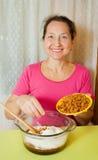 Woman adds raisin into dough Stock Photo