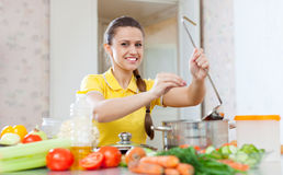 Woman adds spice or salt in saucepan Royalty Free Stock Photo