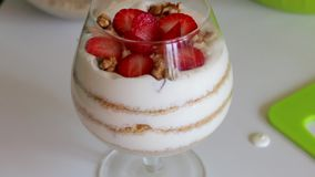A woman adds walnuts to dessert. In the glass layers laid biscuit crumbs and cream. From above ornament from slices of strawberry.