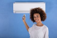 Woman Adjusting Air Conditioner With Remote Control. Young Woman Adjusting Air Conditioner Mounted On Blue Wall With Remote Control royalty free stock photo