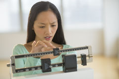 Woman Adjusting Balance Weight Scale At Gym Stock Photos