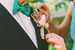 Woman adjusting boutonniere on groom suit Royalty Free Stock Photos
