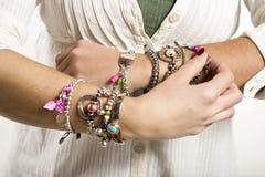 Woman adjusting bracelets closeup image Royalty Free Stock Photos