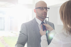 Woman adjusting businessman's tie at home Stock Photo