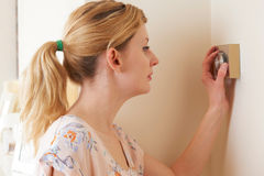 Woman Adjusting Central Heating Thermostat Control. Woman Adjusts  Central Heating Thermostat Control Royalty Free Stock Photo