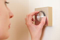 Woman Adjusting Central Heating Thermostat Control. Woman Adjusts  Central Heating Thermostat Control Stock Image