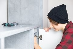 Woman adjusting furniture door at home. royalty free stock photos