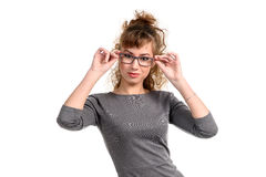 Woman adjusting the glasses. Young woman adjusting the glasses looking at camera isolated on white Royalty Free Stock Images