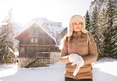 Woman adjusting glove while standing in front of mountain house Royalty Free Stock Photography