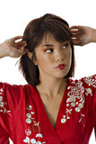Woman adjusting hair. Pretty young asian woman in red traditional kimono pulling hair back Royalty Free Stock Photography