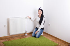 Woman adjusting heating Royalty Free Stock Photography