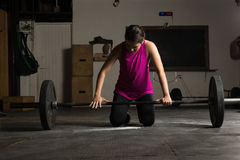 Woman adjusting her grip on a barbell. Portrait of a pretty young woman testing her grip on a barbell before lifting it in a cross-training gym Royalty Free Stock Photo