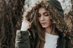 Woman adjusting her hood outdoor. Pretty girl adjusting her fur hood by jacket. Beautiful young woman with blonde hair, wide eyebrows and blue eyes looking at Royalty Free Stock Photography