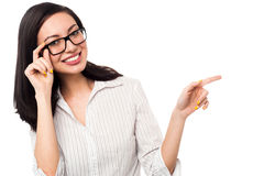 Woman adjusting her spectacles and pointing away Stock Photo