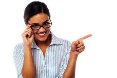 Woman adjusting her spectacles and pointing away Royalty Free Stock Photography