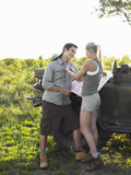 Woman Adjusting Man's Shirt By Jeep Royalty Free Stock Image