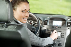 Woman adjusting radio volume in the car. Young smiling woman adjusting radio volume in the car Stock Photos
