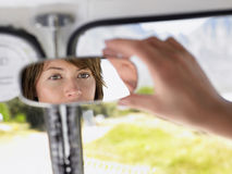 Woman Adjusting Rear View Mirror In Van Stock Image