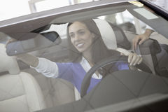 Woman adjusting rearview mirror of her new car Royalty Free Stock Photography